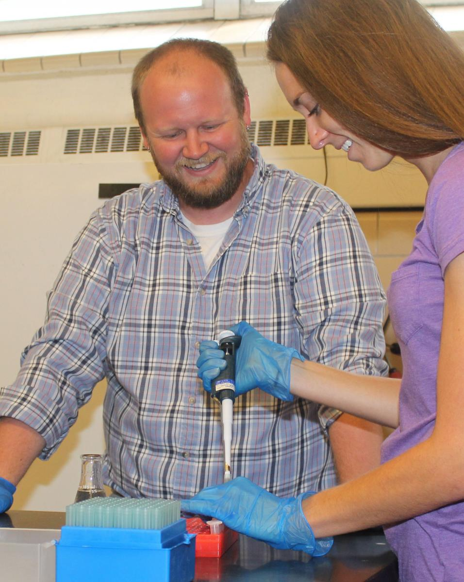 Dr. Eric England instructs a student in his lab.